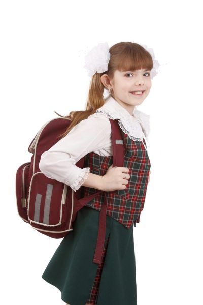 Young school girl ready for school. Little pupil is going to school. Happy young schoolgirl with satchel white background. Portrait of smiling, little girl in school uniform with backpack. Education, learning, teaching.